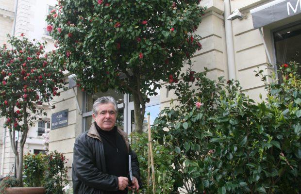 Henri Moulié sous un camélia dont il est fier, devant sa boutique place du Palais Bourbon à Paris