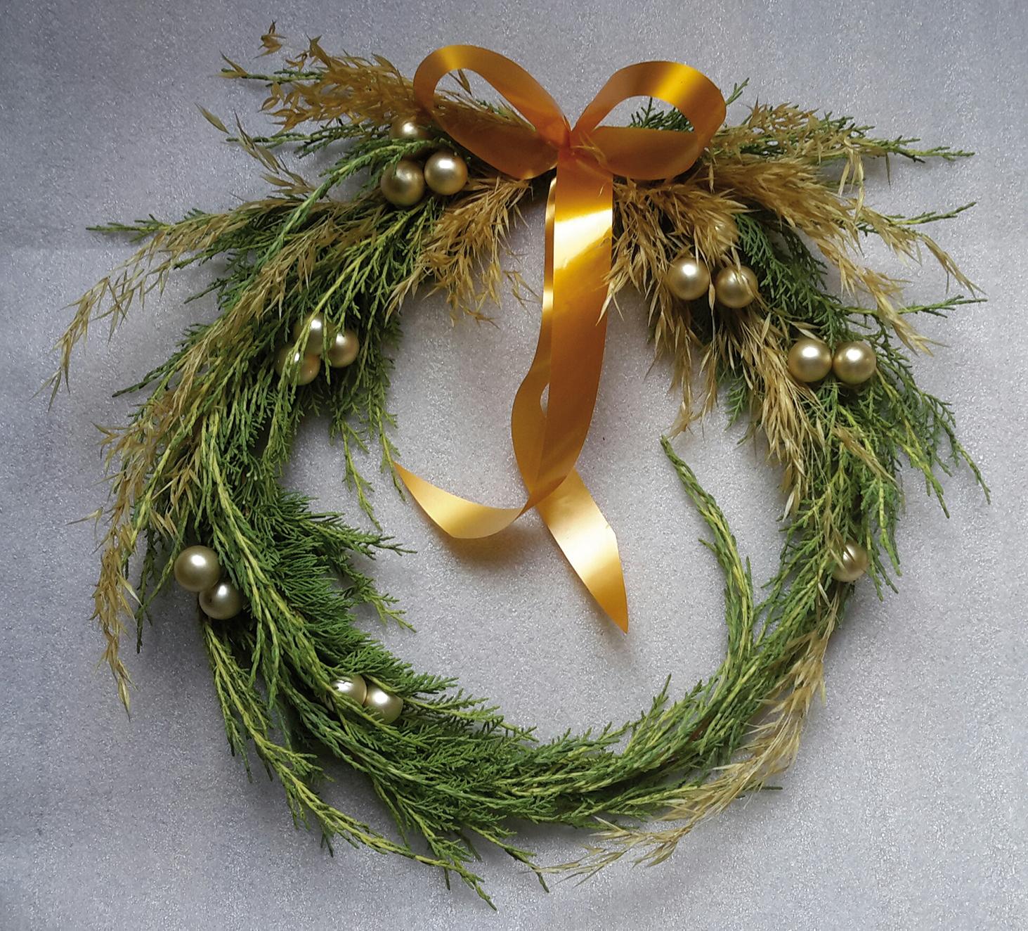 Cette couronne de porte dorée a été réalisée avec un guide en fil de fer, du génévrier de Pfitzer (Juniperus media pfitzeriana) et de la stipe géante (Stipa gigantea)